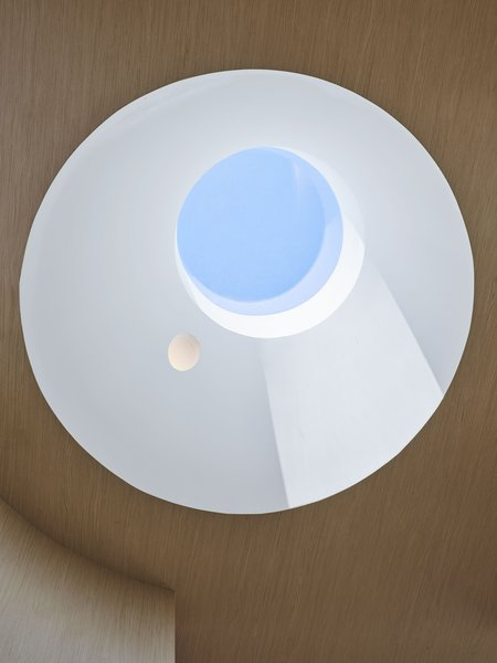 A circular skylight bathes the staircase in light and views of a changing sky.