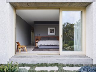 A view of the principal bedroom from the private garden terrace. An Eames molded plywood chair from Matisse sits in the corner. Next to the bed is a Ferm Living Insert side table and a Roy table light from Viabizzuno.
