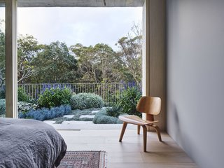 The master bedroom opens up to a private garden terrace and views of the treetops.