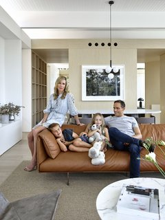 Madeleine Blanchfield sits with her husband Guy, son Aston, and daughter Estelle in their open-plan living room on the top floor of their home.
