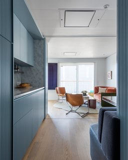 The hall leads to a small galley kitchen, a living space, and glazed sliding doors that open up to a private terrace.