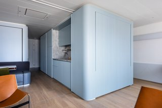To achieve a sense of spaciousness in the eight-foot-tall space, the architects oriented the apartment toward views of the sea and minimized visual clutter with concealed LEDs and continuous aluminum ribs that hide divisions, doors, and appliances.