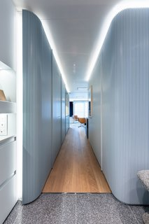 The entry space leads to a hallway between the pair of prefabricated, pod-like volumes. A guest closet lies to the left, and the guest bathroom is on the right.