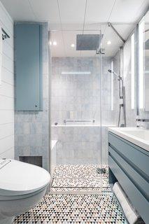 The guest bath features Artistic Tile stone mosaic flooring and walls of Ann Sacks Blue Celeste Field tile and Stone Source Luce Di Ceramica Pumpkin tile.