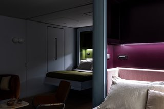 The beds are built of lacquered millwork with custom upholstered headboards in mohair, and they come with integrated nightstands, lighting, and shelving. A sliding door can be used to provide privacy between the two bedrooms.