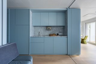 A small galley kitchen is built into the larger of the two prefabricated pod volumes.