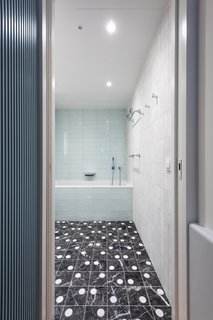 The principal bath is clad in hammered quartzite and white glass, and it features a custom marble tile floor.