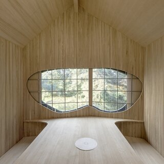 A U-shaped wooden bench wraps around the table used for tea ceremonies. The three-part sliding window is handmade with leaded glass and frames south-facing views of the forest.