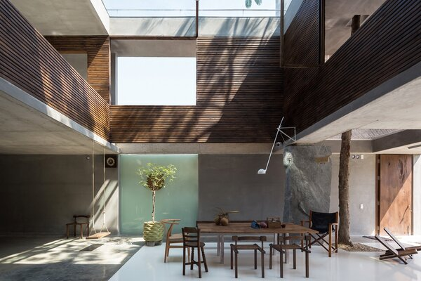 A water-basin skylight illuminates the core of the house—from the roof to the dining area at the heart of the ground-floor living space.
