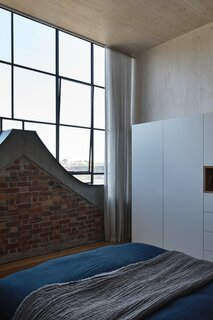 The master bedroom faces a wall of south-facing glass and the top of the Dutch gable.