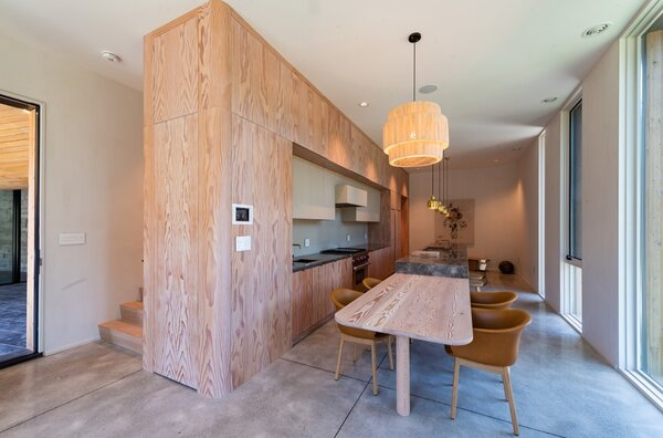 The custom kitchen cabinetry and table are made from Douglas fir. The Elefy dining chairs are by Jaime Hayon for &Tradition, and a Tine K Home pendant lamp hangs above. Polished concrete floors run throughout the space.