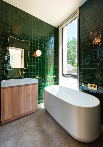 A freestanding Kohler Ceric bath anchors one side of the emerald-tiled bathroom.