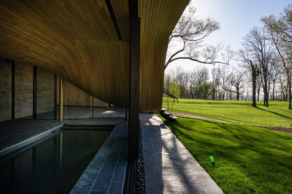 "The structure's ""undulating belly"" is exposed above the cave-like pool pavilion. The floors and outdoor paving feature locally sourced Eramosa limestone, a rock unique to Owen Sound."