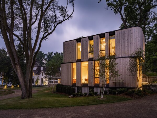 The domino-like residential volumes are staggered on top of each other and feature deeply recessed checkerboard-patterned windows to reduce glare and solar gain. The pavilion is clad in cedar to complement the adjacent stone barn, as well as the property's heirloom trees.