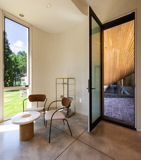 To the side of the guesthouse entrance are a pair of Pavilion lounge chairs by Anderssen & Voll for &Tradition and a Sintra stone table by Frama.