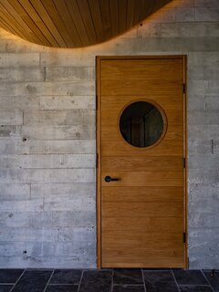 Reclaimed barn boards were used to form the exposed concrete interior walls, which provide thermal mass for significant energy savings. The door with the round window leads to the sauna.