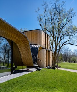 The undulating wood-and-steel structure is engineered to hide a 90-foot steel structural beam that supports the cantilevered canopy and creates the illusion of a floating pavilion from the front.
