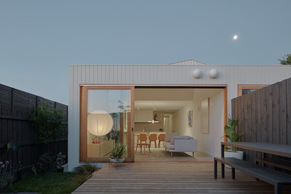 """Glazed sliding doors connect the living spaces to an outdoor deck built with Silvertop ash. Setbacks allow for """"deep pockets of garden,"""" according to the architects."""