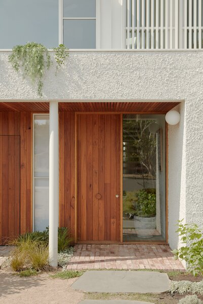 The architects also minimized the appearance of the street-facing garages by concealing the western townhouse's carport behind a timber picket gate and seamlessly integrating the other fully enclosed garage into the facade. Here is a close-up of the deeply recessed eastern townhouse entrance with the concealed carport to the left.