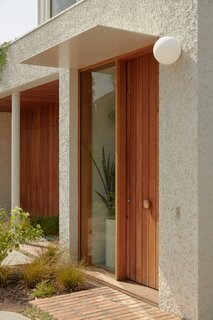 The ground-floor volume is covered warm timber surfaces and stucco render with a Dulux Surfmist paint finish.