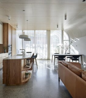 Polished concrete floors harness solar energy through the use of thermal mass. Masson For Light Mort timber-top pendants hang above the kitchen island, which is topped with Carrara marble.