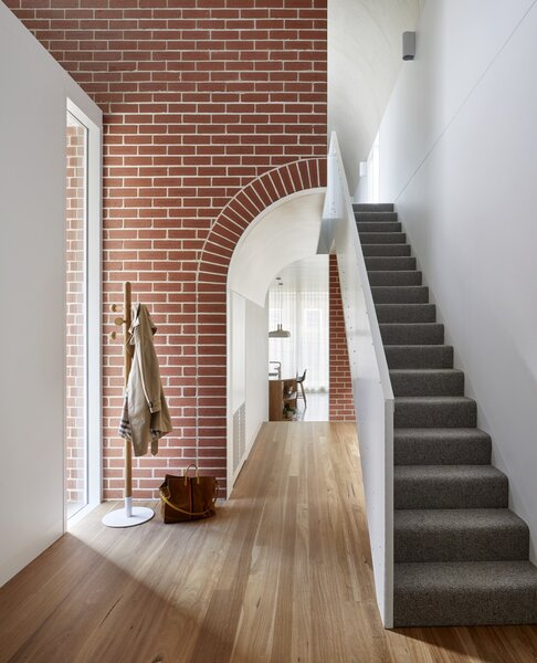 The entry at Deco House opens to the home's sole double-height void. The brick detailing frames the living areas beyond. The stairs on the right lead up to the kids' bedrooms.