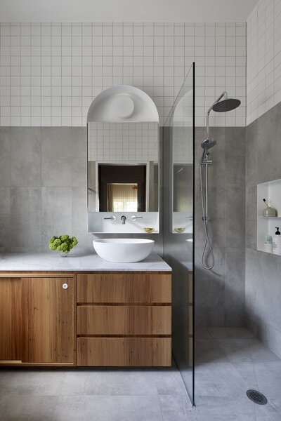The new en suite bath features two-tone, gray-and-white tiles to match the two-tone paintwork in the original house and the two-tone plasterboard on the extension. Metal detailing wraps around the arched mirror above the timber vanity.