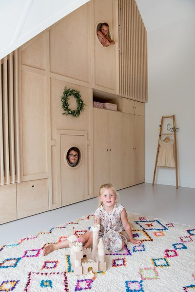 Behind the door of the floor-to-ceiling cabinet in Cato's room is a small play area as well as a staircase that leads to an upper-level play space.