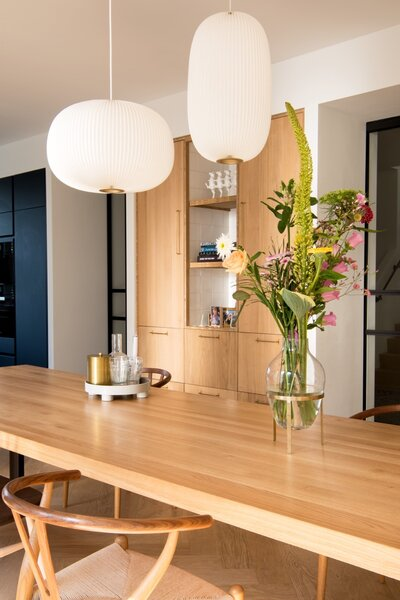 Le Klint pendant lights via Pantoufle hang above the Seuren tafels dining table that's paired with Wishbone chairs.