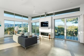 All-Weather 8000 Series double-glazed sliding doors frame views of the landscape and flood the interior with natural light.