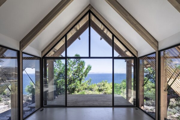 A double-glazed end wall with two doors frames stunning views of the Aegean Sea. A deep roof overhang shelters the outdoor terrace.