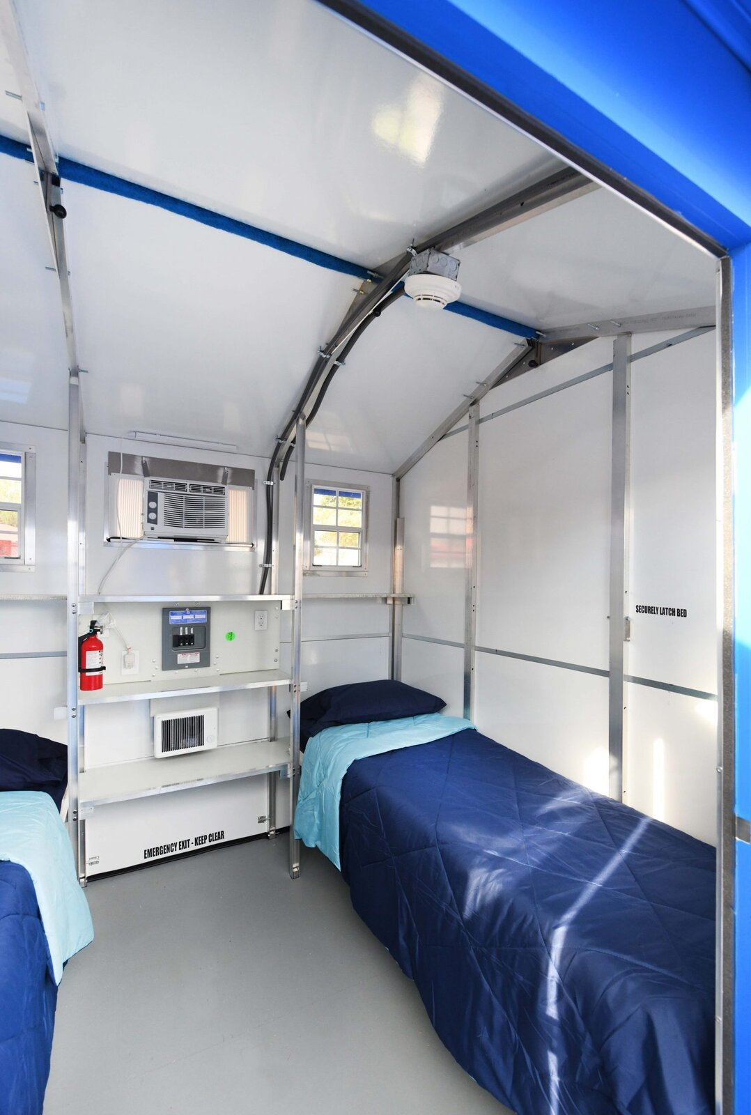 Bedroom, Ceiling Lighting, Storage, and Bed Each prefab includes fold-out beds, storage space, electrical outlets, lighting, heating and air conditioning units, as well as a locking door and windows.  Photo 5 of 12 in L.A. Is Taking On Homelessness With a New, Brightly Colored Tiny Home Village