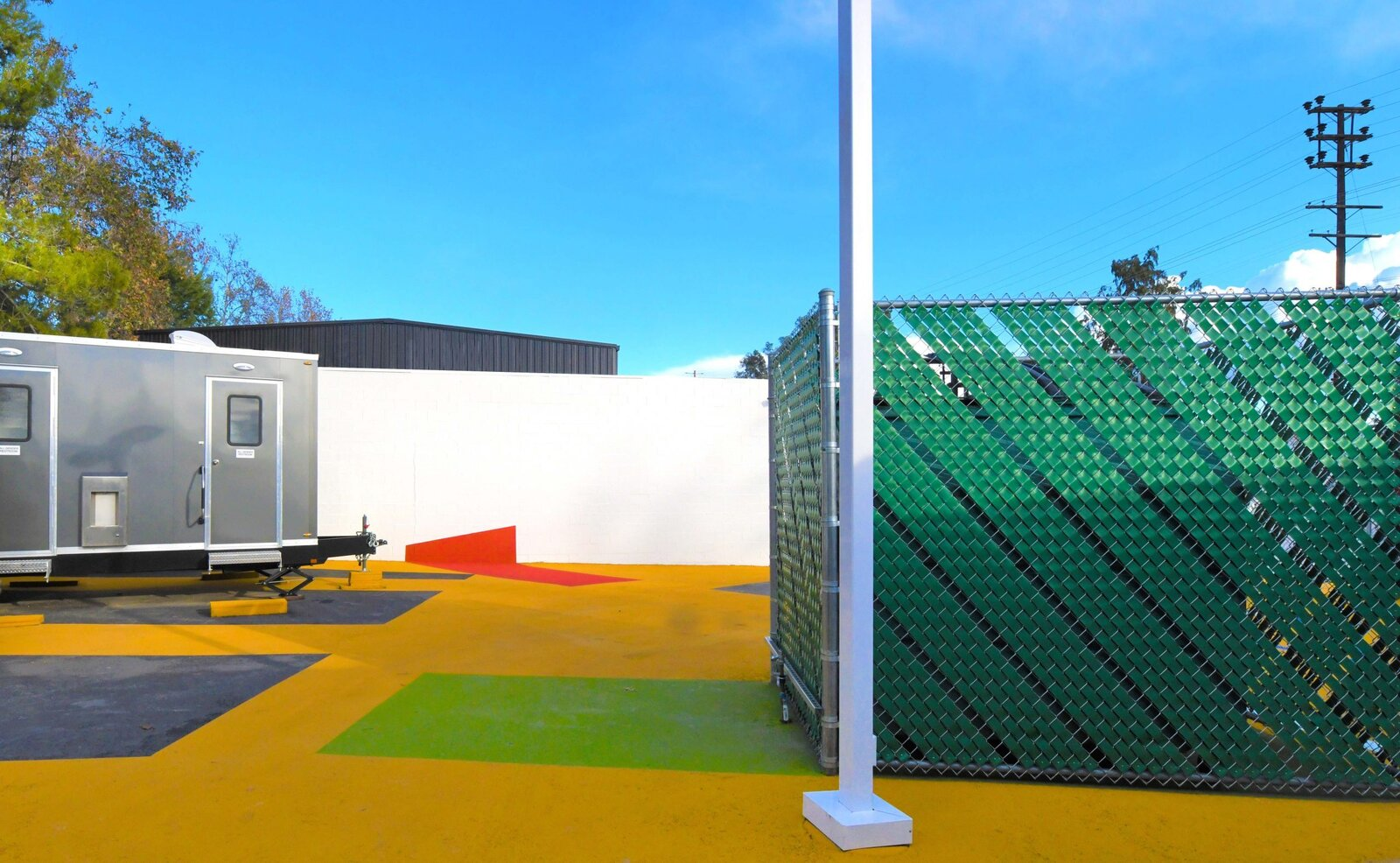 Outdoor, Metal Fences, Wall, and Concrete Patio, Porch, Deck Colorful vinyl strips woven into the tall chain link fences that surround the site are another low-cost way of creating a visually stimulating space.   Photo 9 of 12 in L.A. Is Taking On Homelessness With a New, Brightly Colored Tiny Home Village