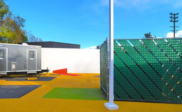 Colorful vinyl strips woven into the tall chain link fences that surround the site are another low-cost way of creating a visually stimulating space.