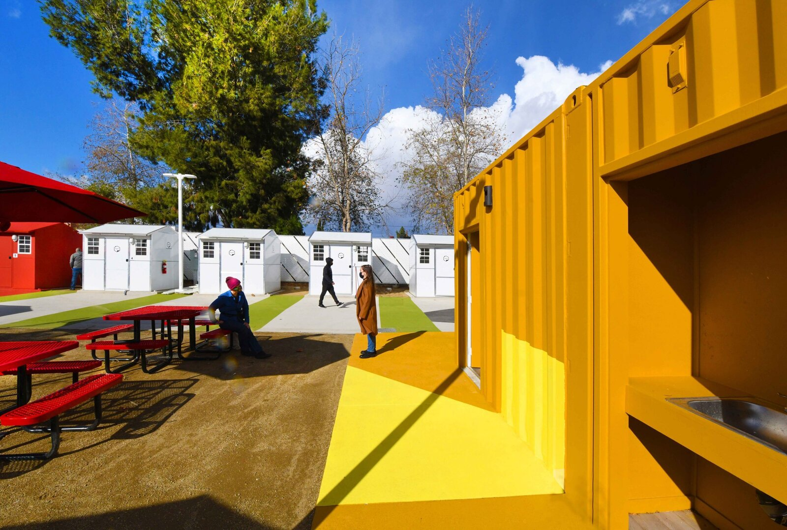 Exterior, Prefab Building Type, Tiny Home Building Type, and Gable RoofLine Safety is emphasized with video surveillance and 24-hour security. No alcohol is allowed on site and there is a curfew.   Photo 11 of 12 in L.A. Is Taking On Homelessness With a New, Brightly Colored Tiny Home Village