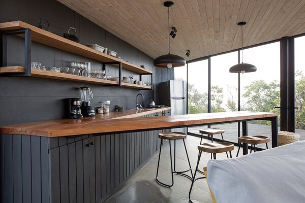 Blackened pine continues from the exterior to the interior, where it's used for the kitchen backsplash and cabinetry. The countertops and open shelving are made from oak.