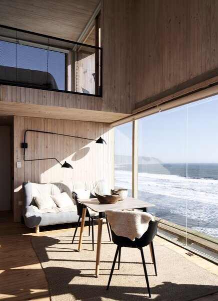 """""""On the first floor, we decided to open the cabins up to views with a floor-to-ceiling window that connects the living area to the sea,"""" explains Felipe Croxatto. """"In the second-floor bedroom, we frame select views through smaller windows."""""""