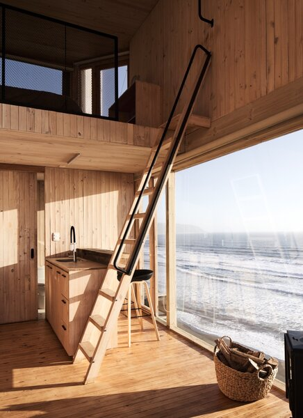 A wooden ladder leads up to the loft bedroom. A wood-burning stove provides heating.