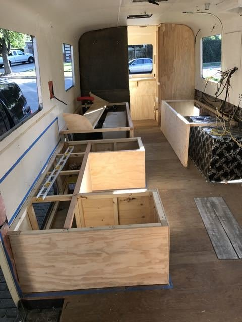"Modern home with Living Room, Bench, and Storage. Cabinet building in process. Everything is framed and built from stratch. Photo 7 of Flatnose Frank: Our Renovated Vintage RevCon Motorhome (""Is that an Airstream?"")"