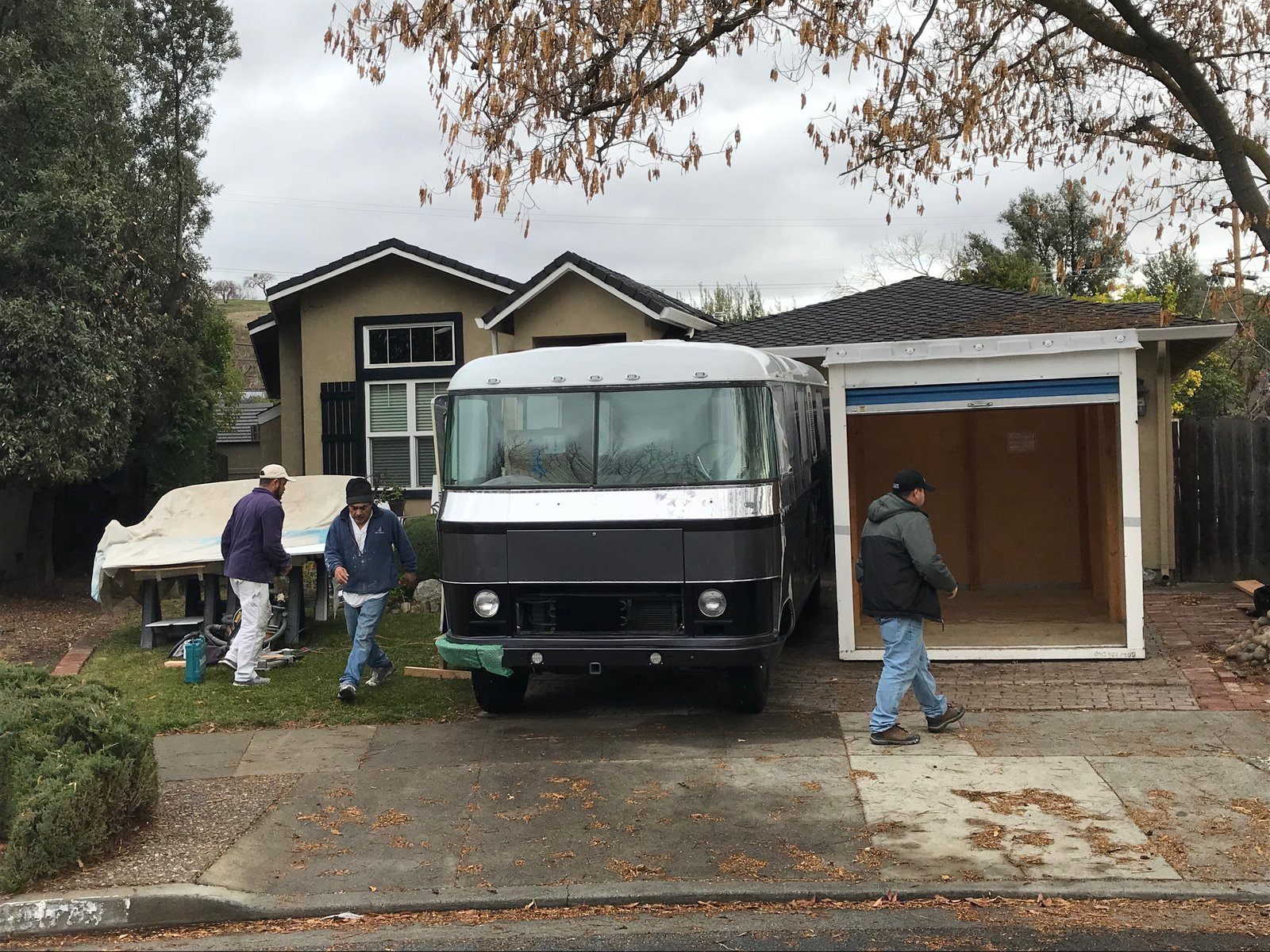 "Cabinet installation in progress. This crew of brothers from Pride Painting went above and beyond helping with our crazy project. (The temp storage from PODS housed all the cabinetry while the RevCon was in the body shop.) Photo 8 of Flatnose Frank: Our Renovated Vintage RevCon Motorhome (""Is that an Airstream?"") modern home"