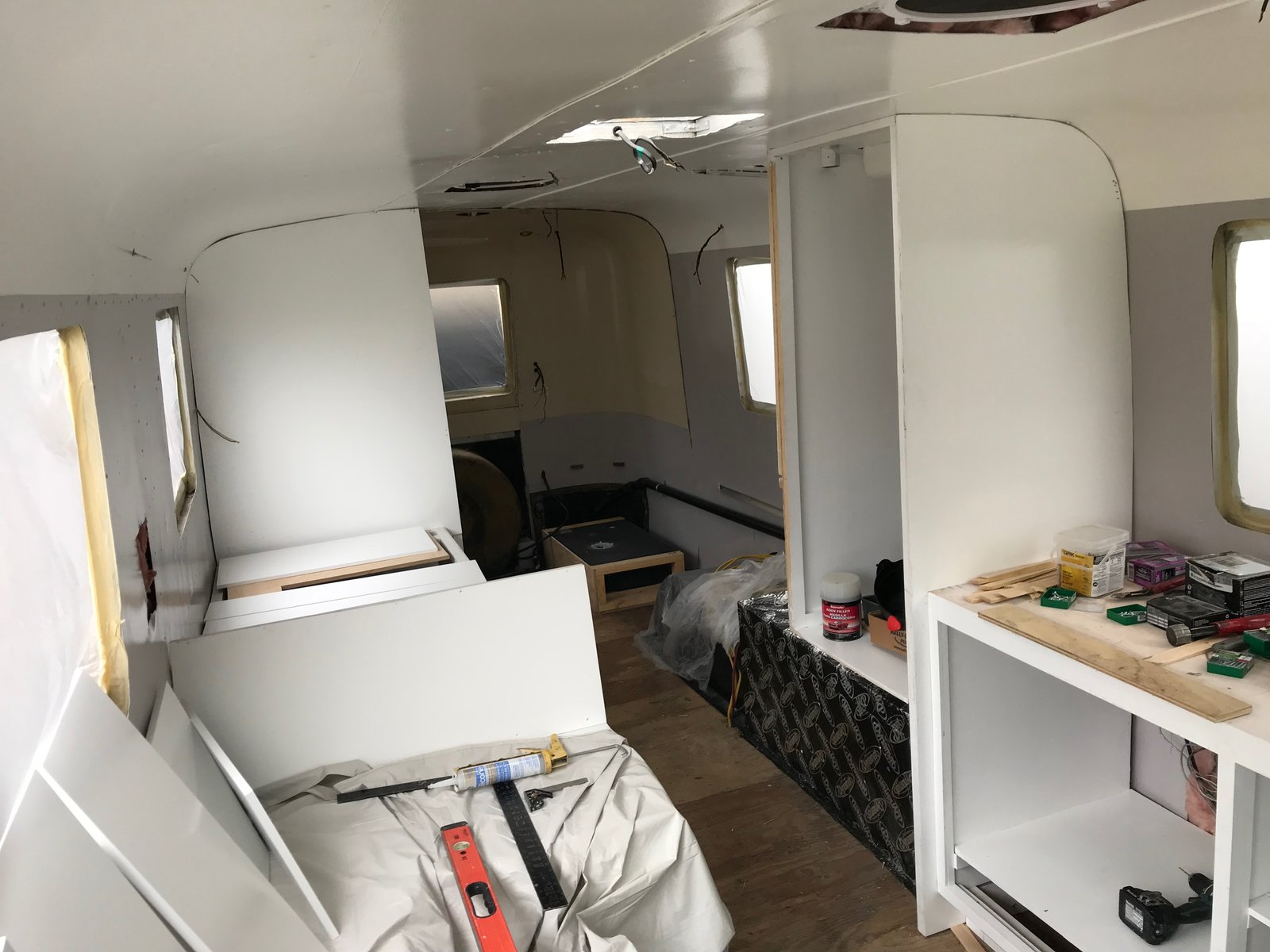 "Modern home with Living Room. Cabinet installation continues with semi-gloss white paint. Photo 9 of Flatnose Frank: Our Renovated Vintage RevCon Motorhome (""Is that an Airstream?"")"