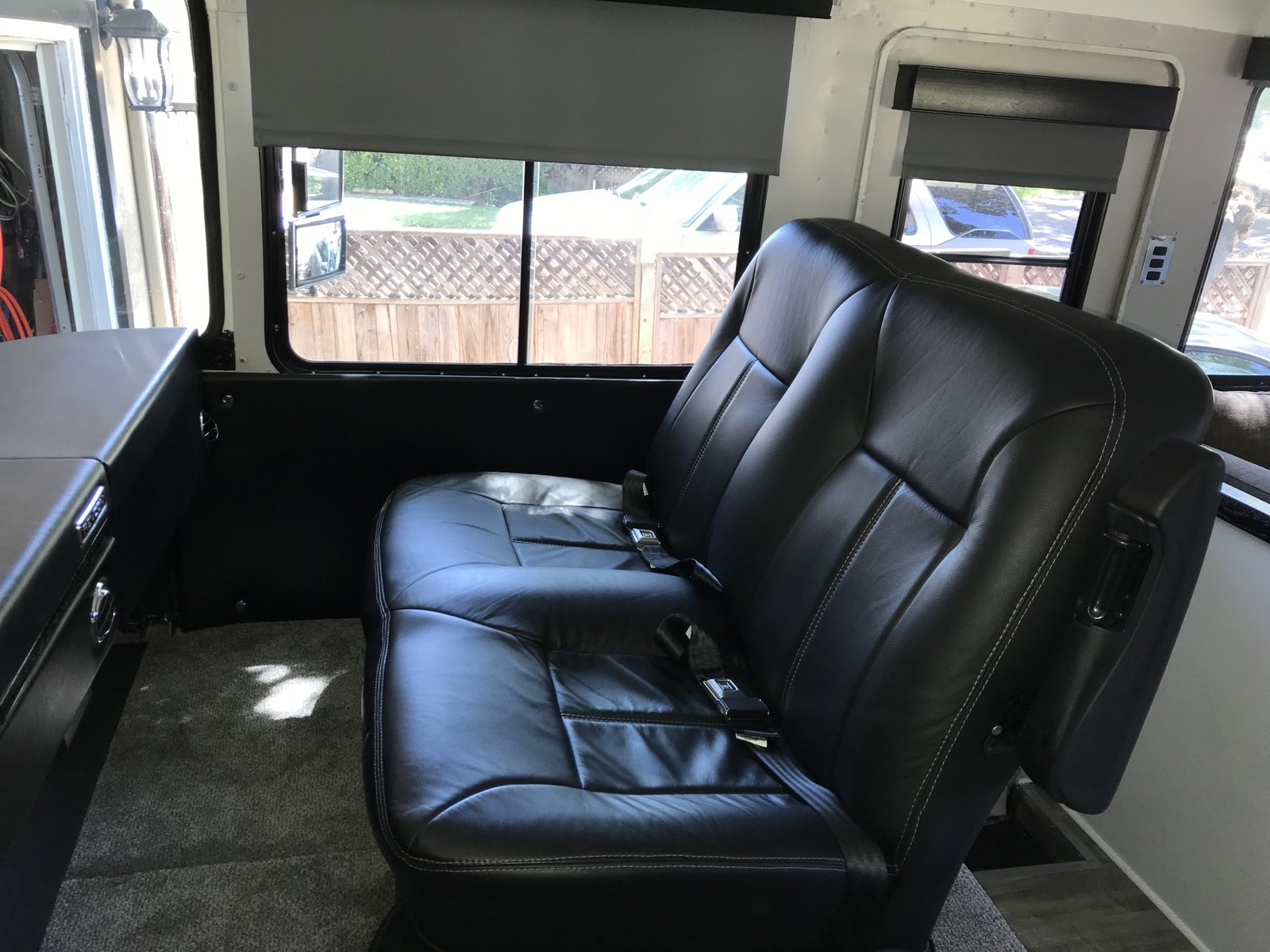 "This is the original two-passenger front seat from RevCon, reupholstered to match the leather driver's seat. Photo 14 of Flatnose Frank: Our Renovated Vintage RevCon Motorhome (""Is that an Airstream?"") modern home"