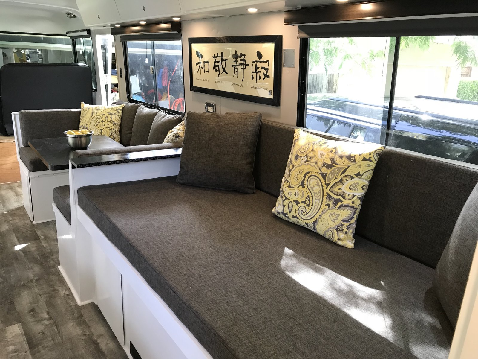 "Right rear couch / double bed with inspiration paisley fabric on pillows. Cushions, leather seats and pillows were all stitched masterfully by Barrios Upholstery in Morgan Hill, CA. Photo 18 of Flatnose Frank: Our Renovated Vintage RevCon Motorhome (""Is that an Airstream?"") modern home"
