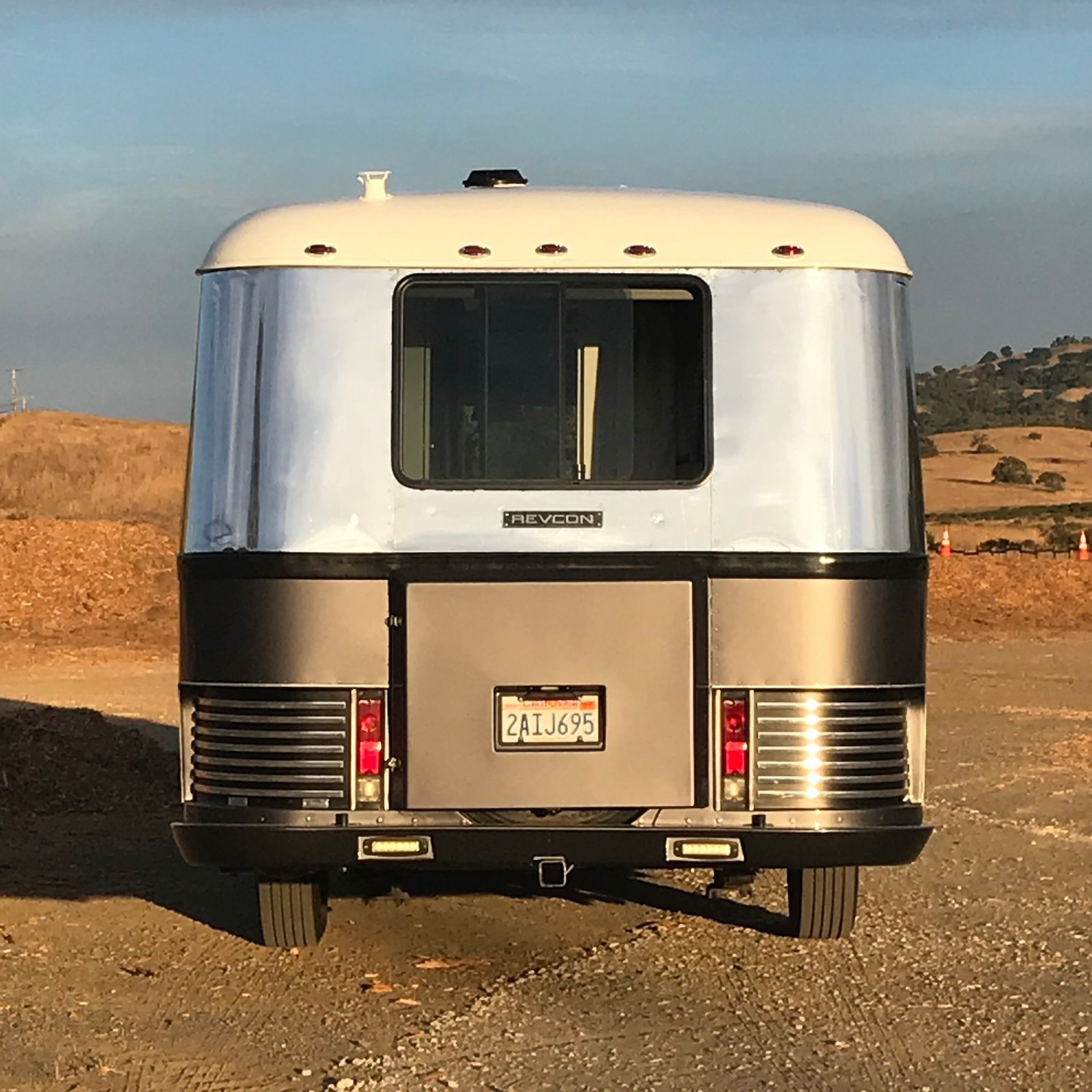 "Rear view. Aluminum trim prieces were a huge polishing job. LED floodlights inset in custom bumper shed great light for setting up camp! Photo 21 of Flatnose Frank: Our Renovated Vintage RevCon Motorhome (""Is that an Airstream?"") modern home"