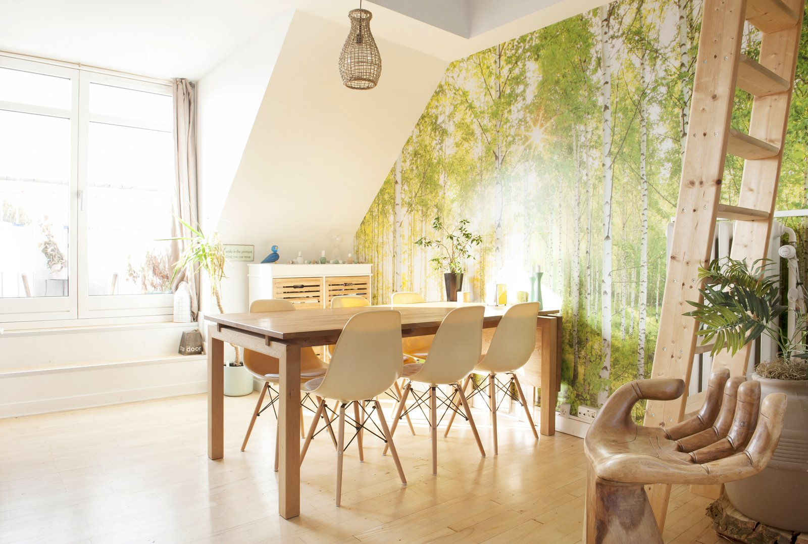 Dining Room, Table, Stools, Pendant Lighting, and Medium Hardwood Floor bright dining area with wooden furniture, live plants, and forest wallpaper  Bringing Nature Inside by Petra Ford