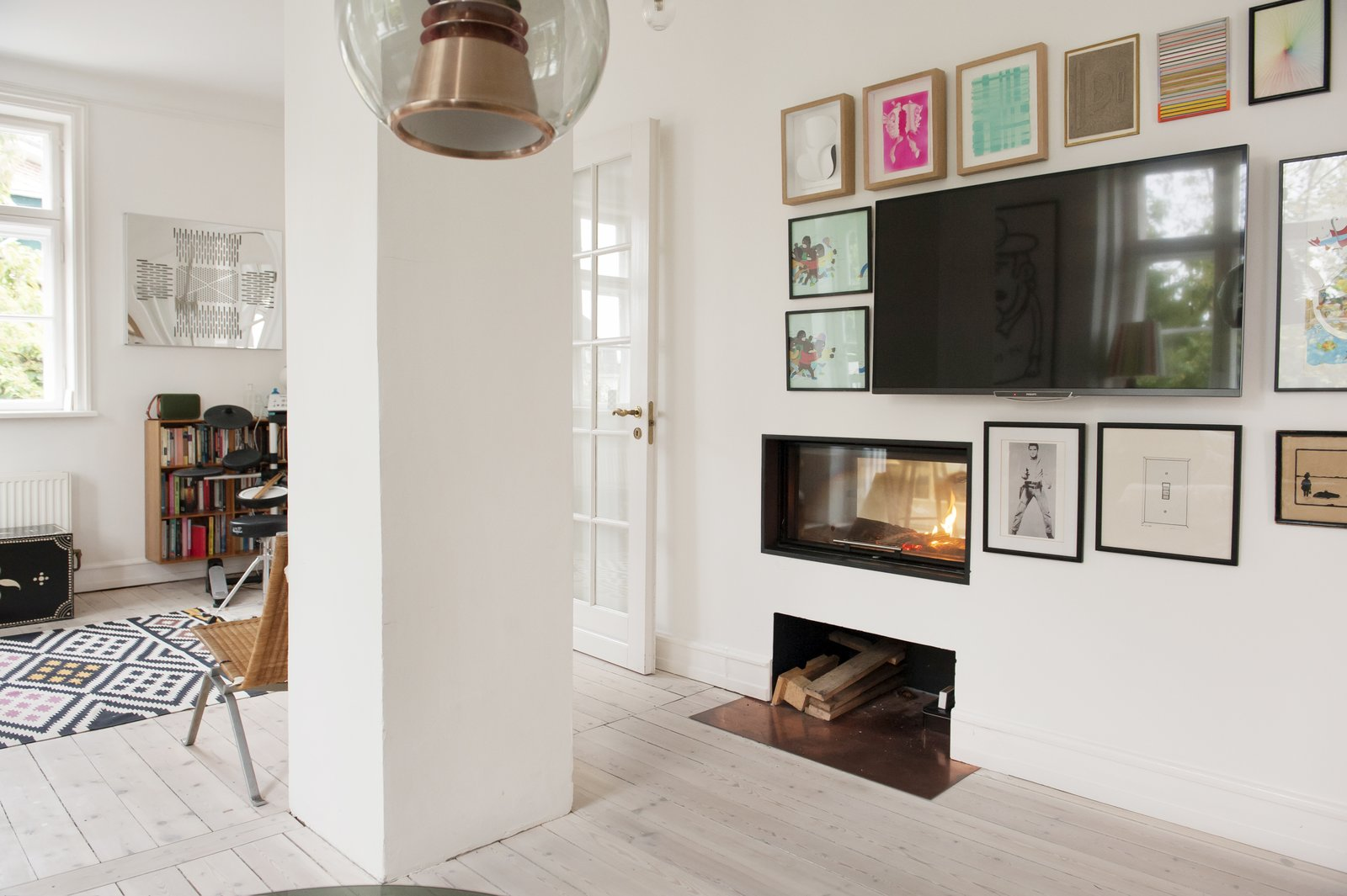 Living Room, Pendant Lighting, Light Hardwood Floor, and Wood Burning Fireplace Framed artwork and a sleek rectangular built-in fireplace leave the television almost unnoticed.  Colorful & Eclectic Danish Home by Petra Ford