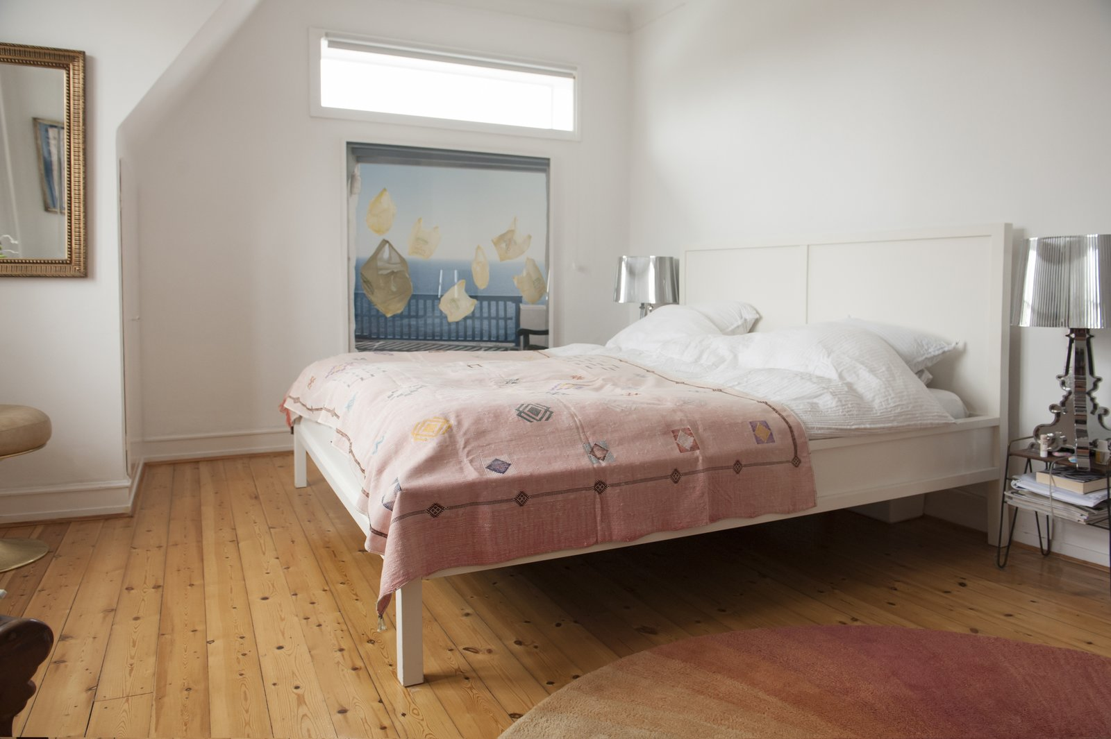 Bedroom, Bed, Night Stands, Table Lighting, and Medium Hardwood Floor Color plays a key role in the master bedroom, which plays with pinks and blues.  Colorful & Eclectic Danish Home by Petra Ford