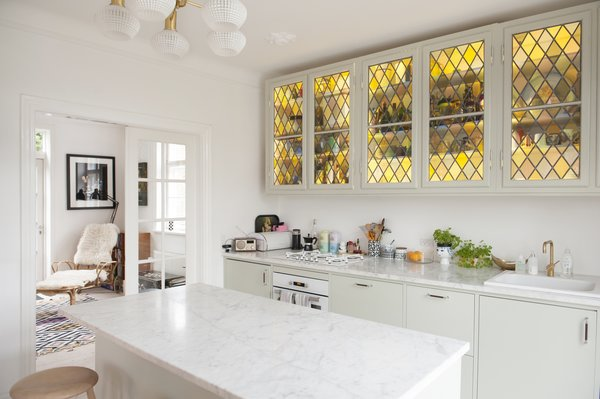 Sleek white kitchen is given a pop of color and old world charm with yellow stained glass cabinets. Luxurious marble countertop and island are also featured.