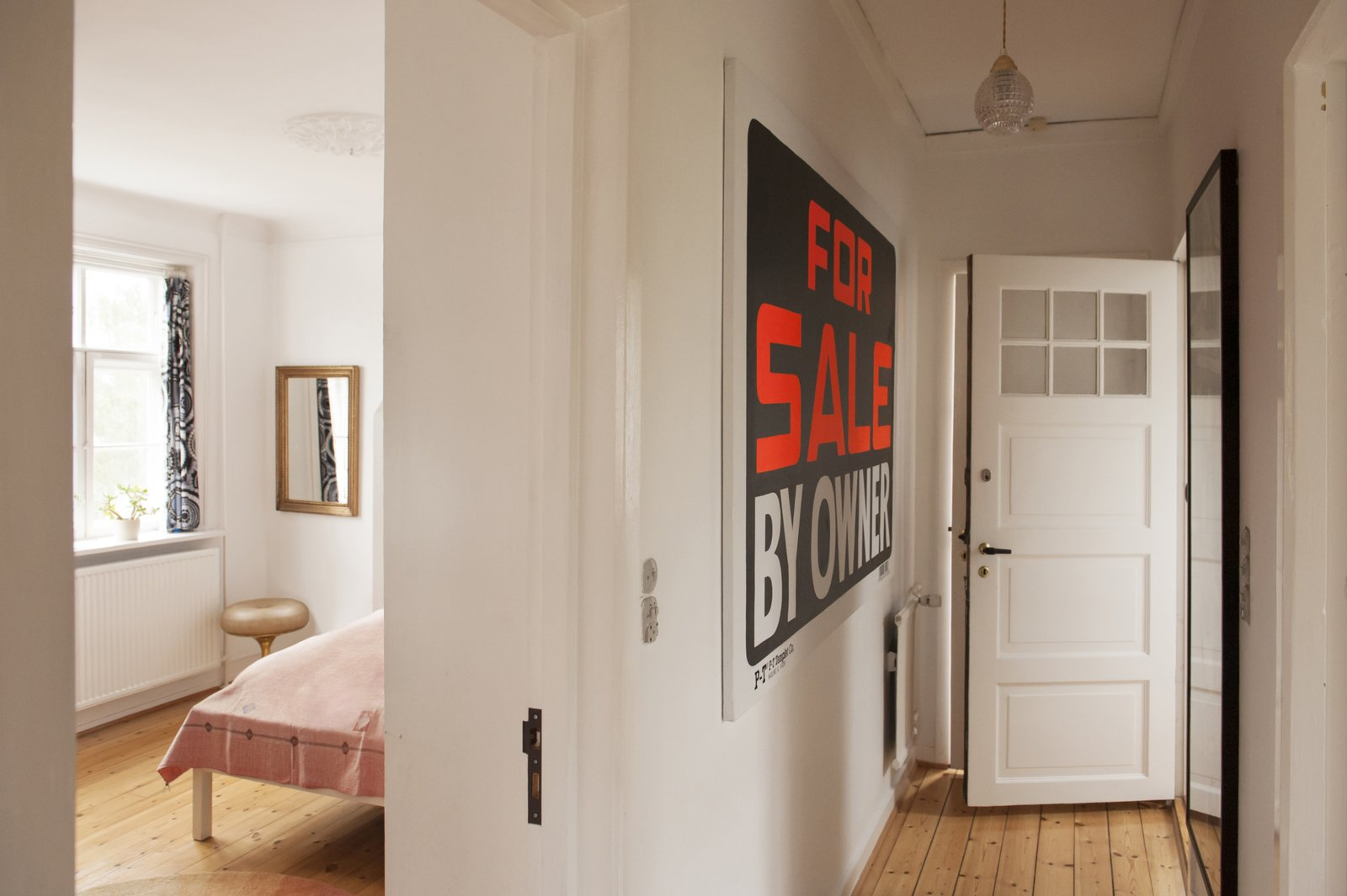 Hallway and Medium Hardwood Floor A black and neon orange For Sale sign hangs in the hallway outside the master bedroom, adding a bit of whimsy to the space.  Colorful & Eclectic Danish Home by Petra Ford