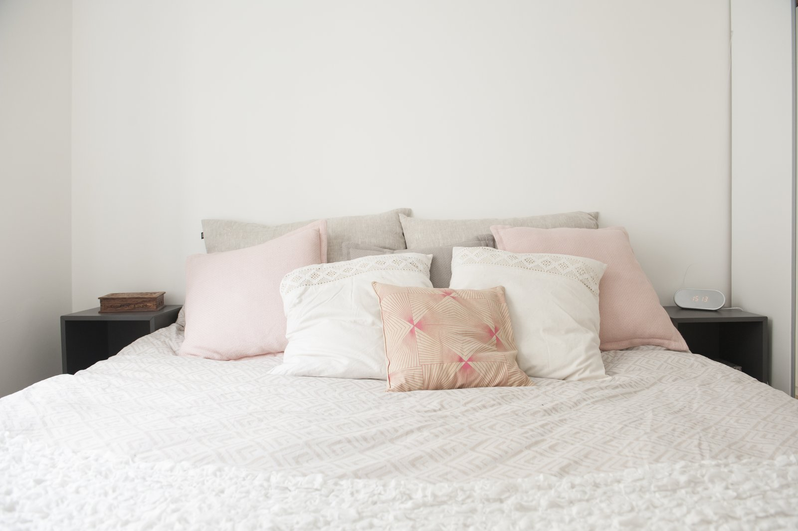 Bedroom and Bed pink and white pillows atop an earth-toned bed  Pretty and Sweet Family Flat by Petra Ford